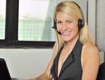 Schöne blonde Frau im Sitzungssaal mit Kopfhörer Lizenzfreies Stockbild