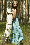 Schöne blonde Frau im Sommerwald Lizenzfreie Stockfotografie