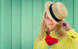 Schöne blonde Frau im Strohhut, der eine rote Blume hält Lizenzfreies Stockfoto