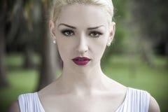 Schöne blonde Frau im weißen Kleid Stockbilder