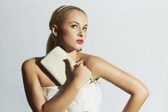 Schöne blonde Frau im weißen Kleid Stilvolles Mädchen der Mode mit weißer Kupplung Rote Lippen Braut Lizenzfreie Stockfotografie