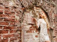 Schöne blonde Frau im weißen Spitzekleid Stockfotografie