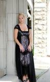 Schöne blonde Frau im Weinleseschwarzkleid Stockfotografie