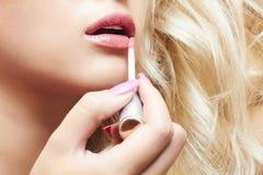 Schöne blonde Frau malt Lippen mit Lippenstift. Lipgloss Lizenzfreies Stockbild