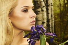 Schöne blonde Frau mit blauen Blumen in einem Wald Lizenzfreies Stockfoto