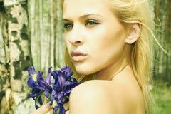 Schöne blonde Frau mit blauen Blumen in einem Wald Stockbild