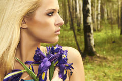 Schöne blonde Frau mit blauen Blumen in einem Wald Stockfotos