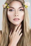 Schöne blonde Frau mit Blumen auf ihrem Kopf Lizenzfreies Stockbild
