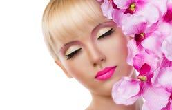 Schönes blondes Mädchen mit Blumen und rosa Make-up Stockfotografie