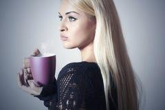 Schöne blonde Frau mit Coffee.Cup des Tees. Heißes Getränk Stockfoto