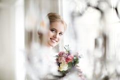 Schöne blonde Frau mit dem Blumenstrauß, der in einem Hochzeitskleid aufwirft Lizenzfreies Stockbild