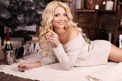Schöne blonde Frau mit dem Champagner, der neben Weihnachtsbaum aufwirft Stockfotografie