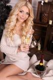 Schöne blonde Frau mit dem Champagner, der neben Weihnachtsbaum aufwirft Lizenzfreies Stockbild