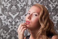 Schöne blonde Frau mit dem Finger auf ihren Lippen Stockbilder