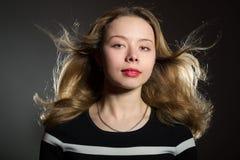 Schöne blonde Frau mit dem Fliegenhaar Stockfotografie