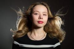 Schöne blonde Frau mit dem Fliegenhaar Stockfotos