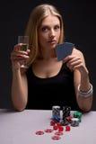 Schöne blonde Frau mit dem Glas Champagner Poker spielend Stockbilder