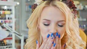 Schöne blonde Frau mit dem langen gelocktes Haar- und Artmake-up, das an der Kamera aufwirft Stockfotos