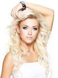 Schöne blonde Frau mit dem langen lockigen Haar Stockfotografie