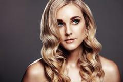 Schöne blonde Frau mit dem lockigen Haar Lizenzfreie Stockbilder