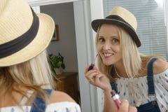 Schöne blonde Frau mit dem Spiegel, der Lipgloss setzt Lizenzfreie Stockfotos