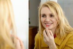 Schöne blonde Frau mit dem Spiegel, der Lipgloss setzt Stockbilder