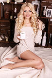 Schöne blonde Frau mit dem Tasse Kaffee, werfend neben Weihnachtsbaum auf Lizenzfreie Stockbilder