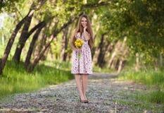 Schöne blonde Frau mit den gelben Blumen im Freien Stockbilder