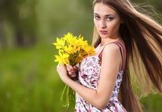 Schöne blonde Frau mit den gelben Blumen im Freien Stockfoto