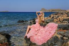 Schöne blonde Frau mit den langen Beinen in einem rosa Ballkleid Lizenzfreies Stockfoto