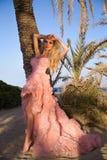 Schöne blonde Frau mit den langen Beinen in einem rosa Ballkleid Stockbild