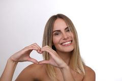 Schöne blonde Frau mit den nackten Schultern, die ein Herz mit ihren Händen bilden Lizenzfreie Stockbilder