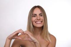 Schöne blonde Frau mit den nackten Schultern, die ein Herz mit ihren Händen bilden Lizenzfreie Stockfotografie