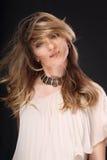 Schöne blonde Frau mit der langen gelockten Frisur, die das Haar rüttelt Lizenzfreie Stockbilder