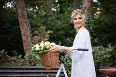 Schöne, blonde Frau mit einem Fahrrad in einem Park Lizenzfreie Stockfotografie