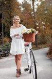 Schöne, blonde Frau mit einem Fahrrad in einem Park Lizenzfreies Stockbild