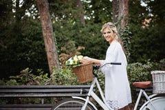 Schöne, blonde Frau mit einem Fahrrad in einem Park Stockbilder
