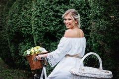 Schöne, blonde Frau mit einem Fahrrad in einem Park Lizenzfreie Stockfotos