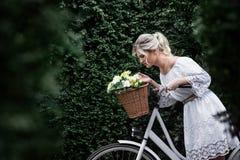 Schöne, blonde Frau mit einem Fahrrad in einem Park Lizenzfreies Stockfoto