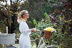Schöne, blonde Frau mit einem Fahrrad in einem Park Lizenzfreie Stockbilder