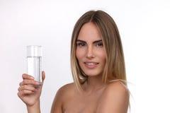 Schöne blonde Frau mit einem Glas Wasser Stockfotografie