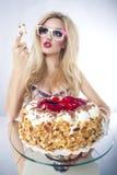 Schöne blonde Frau mit einem Kuchen Lizenzfreie Stockbilder