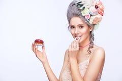 Schöne blonde Frau mit einem Kuchen Süße sexy Dame Abbildung der roten Lilie Art und Weisefoto Stockfotografie