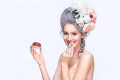 Schöne blonde Frau mit einem Kuchen Süße sexy Dame Abbildung der roten Lilie Art und Weisefoto Stockfotos