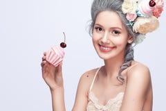 Schöne blonde Frau mit einem Kuchen Süße sexy Dame Abbildung der roten Lilie Art und Weisefoto Lizenzfreies Stockbild