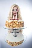 Schöne blonde Frau mit einem Kuchen. Süße sexy Dame mit Gläsern Stockfotografie