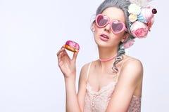 Schöne blonde Frau mit einem Kuchen Süße sexy Dame mit Herzgläsern Abbildung der roten Lilie Art und Weisefoto Lizenzfreie Stockfotos