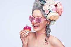 Schöne blonde Frau mit einem Kuchen Süße sexy Dame mit Herzgläsern Abbildung der roten Lilie Art und Weisefoto Stockbild