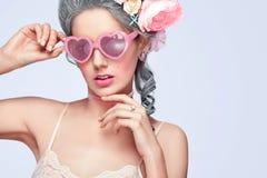Schöne blonde Frau mit einem Kuchen Süße sexy Dame mit Herzgläsern Abbildung der roten Lilie Modefoto mit Kopienraum Lizenzfreie Stockfotografie
