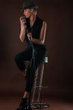 Schöne blonde Frau mit einem Mikrofon, das auf Barhocker sitzt Stockfotografie